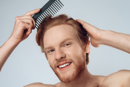 Pleased red haired man combs hair with comb. Isolated on grey background. Studio portrait. Male beauty.