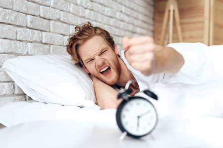 Young, irritated man reaches out to turn off ringing alarm clock. Morning awakening. Waking up.