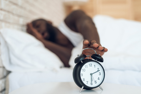 African American man does not want to wake up, turning off alarm. Sweet dreams. Waking up.