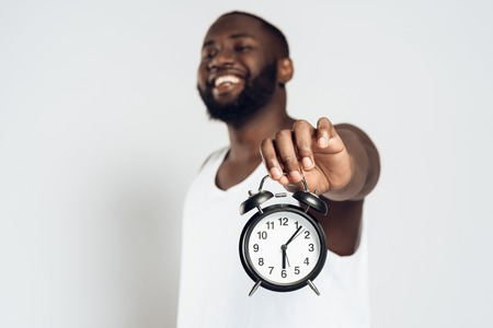 African American smiling man posing with alarm clock in hands. Time is running. Clock is ticking. Isolated on white background. Studio portrait.