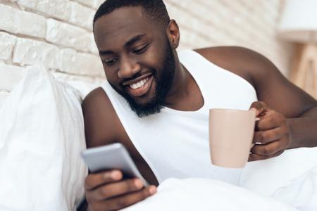 Black, awakened man drinks coffee in bed browsing web. Early morning. Pleasant awakening.