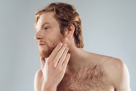Red haired young man is stroking beard. Morning hygiene procedures. Isolated on grey background. Studio portrait. Skin care.