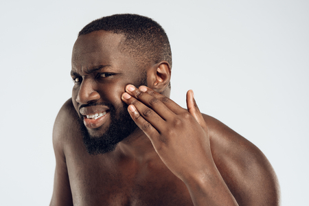 African American man looks at pimples on face. Acne. Male hygiene. Isolated on white background. Studio portrait.