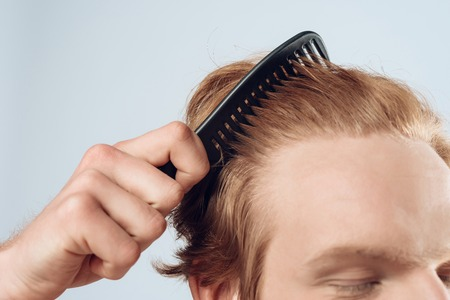 Close up. Pleased red haired man combs hair with comb. Isolated on grey background. Studio portrait. Male beauty. 写真素材