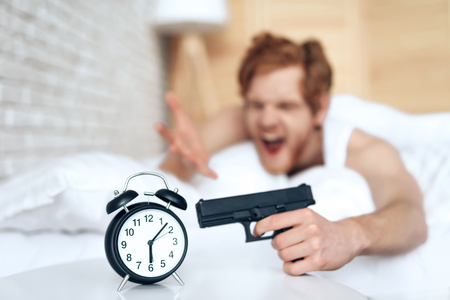 Woken up evil man is aims gun at alarm clock, lying in bed. Lack of sleep. Morning awakening. Waking up. Stock Photo