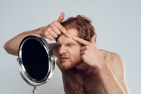 Red haired young man squeeze out pimple on forehead, looking into mirror. Morning hygiene procedures. Isolated on grey background. Studio portrait. Acne. Skin care.