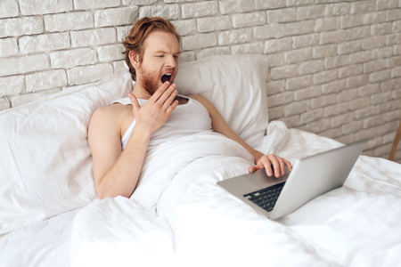 Red haired young guy works with laptop, yawning early morning. Contemporary freelancer works with computer in bed at morning .