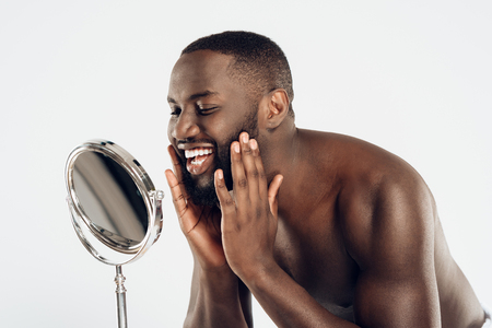 African American man uses moisturizing lotion, looking in mirror. Male hygiene. Isolated on white background. Studio portrait.