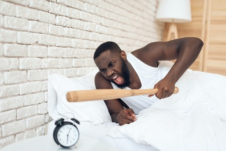 African American angry man threatens baseball bat with alarm clock. Waking up. Morning awaking.
