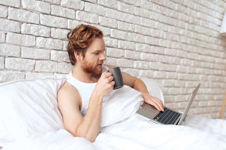 Red haired awaking man lies in bed with laptop while drinking coffee. Successful businessman is working in morning with laptop.