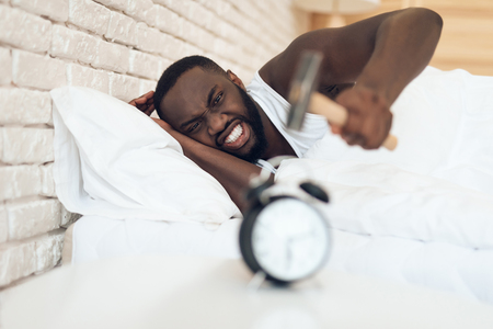 African American man is hammering alarm clock. Waking up.