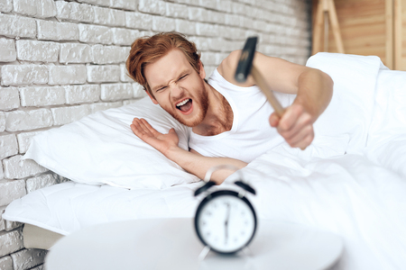 Young red haired man hammers alarm clock. Lack of sleep. Morning awakening. Waking up. 版權商用圖片