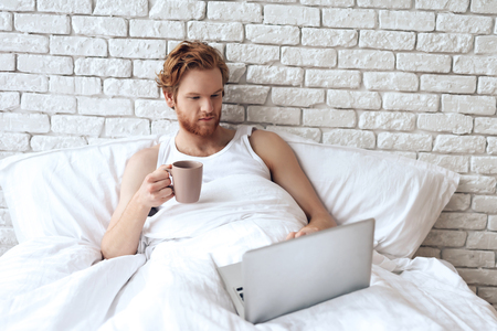 Red haired awaking man lies in bed with laptop while drinking coffee. Successful businessman is working in morning with notebook.