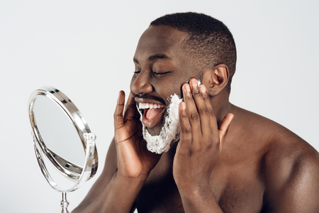 African American man smears shaving cream on face. Isolated on white background. Studio portrait. Male hygiene. Morning hygiene procedures.
