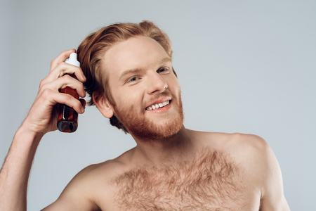 Red haired hairy man sprinkles balm on hair. Hair care. Isolated on grey background. Studio portrait. Male beauty concept.