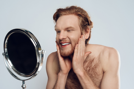 Red haired young man stroking beard, looking in mirror. Morning hygiene procedures. Isolated on grey background. Studio portrait.