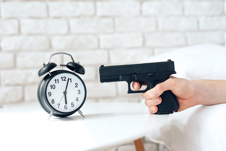 Woken up man is aims gun at alarm clock, lying in bed. Lack of sleep. Morning awakening. Waking up.