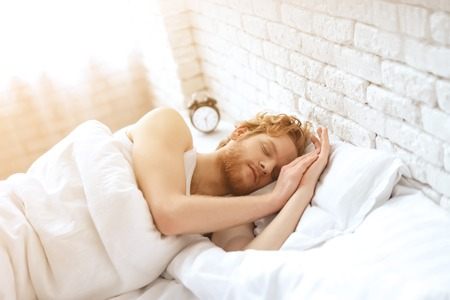 Young redhead man sleeps under white blanket. Sweet dreams. Waking up. Healthy sleep.