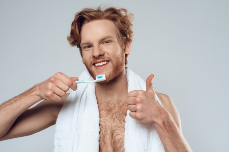 Red haired smiling man is brushing teeth. Healthy lifestyle. Male hygiene. Isolated on grey background. Studio portrait.