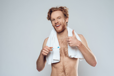 Redheaded smiling man with toothbrush is showing thumbs up. Morning hygiene procedures. Isolated on grey background. Studio portrait.