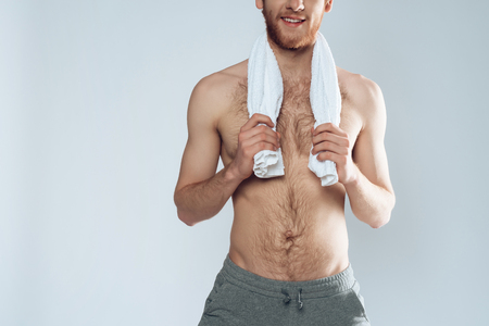 Red haired bearded man is standing with towel. Personal hygiene. Isolated on grey background. Studio portrait.