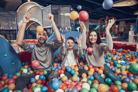 Happy family in pool with balls. Family rest, leisure concept. Spending holiday together. Entertainment center, mall, amusement park.