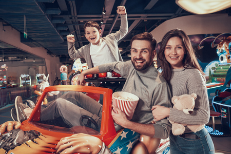 Happy family sitting on toy car. Rest, holiday, leisure. Spending time together. Entertainment center, mall, amusement park.