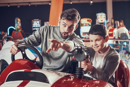 Joyfull father and son sitting on toy car. Spending holiday together with family. Entertainment center, mall, amusement park. Family rest, leisure concept.
