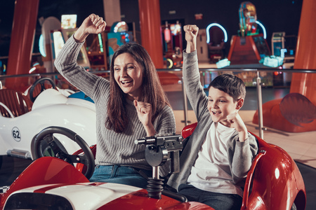 Happy smiling mother and son in amusement center. Spending holiday together with family. Entertainment center, mall, amusement park. Family rest, leisure concept. Stock Photo