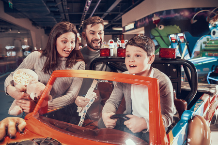 Happy family, enraptured son sitting on toy car. Rest, holiday, leisure. Spending time together. Entertainment center, mall, amusement park. Stock Photo