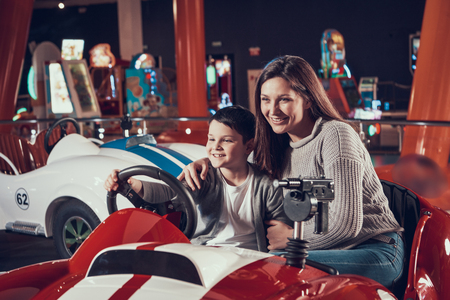 Happy smiling mother and son sitting on toy car. Spending holiday together with family. Entertainment center, mall, amusement park. Family rest, leisure concept. Stock Photo