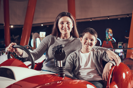 Smiling mother and son in amusement center. Spending holiday together with family. Entertainment center, mall, amusement park. Family rest, leisure concept.
