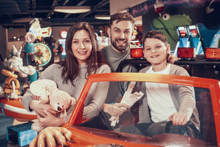 Happy family, son sitting on toy car. Family rest, leisure. Spending holiday together with family. Entertainment center, mall, amusement park.