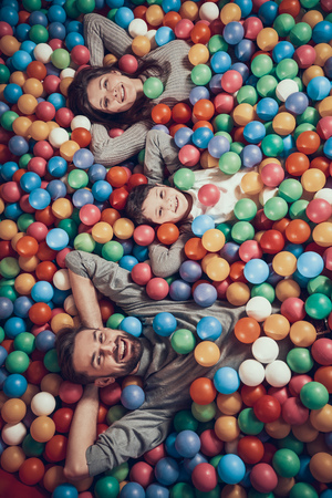Top view. Happy family lying in pool with balls. Family rest, leisure concept. Spending holiday together. Entertainment center, mall, amusement park. Banco de Imagens - 103343183
