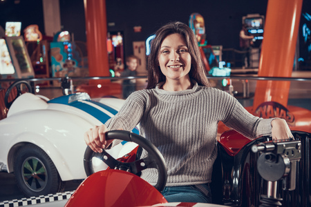 Women in amusement center sitting in toy car. Family rest, leisure. Spending holiday together with family. Entertainment center, mall, amusement park. Archivio Fotografico