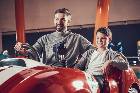 Amused smiling father and son sitting on toy car. Spending holiday together with family. Entertainment center, mall, amusement park. Family rest, leisure concept. Stock Photo