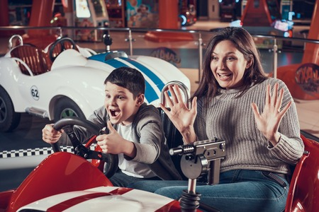 Happy mother and son sitting on toy car. Spending holiday together with family. Entertainment center, mall, amusement park. Family rest, leisure concept.