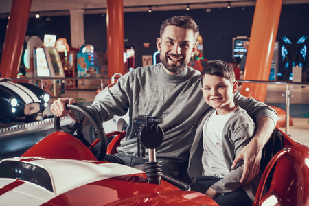 Happy smiling father and son sitting on toy car. Spending holiday together with family. Entertainment center, mall, amusement park. Family rest, leisure concept.