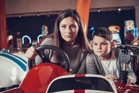 Concentrated mother and son driving toy car. Spending holiday together with family. Entertainment center, mall, amusement park. Family rest, leisure concept.