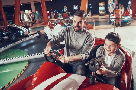 Smiling father and son in amusement center. Spending holiday together with family. Entertainment center, mall, amusement park. Family rest, leisure concept.