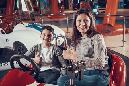 Happy smiling mother and son in toy car. Spending holiday together with family. Entertainment center, mall, amusement park. Family rest, leisure concept. Stock Photo