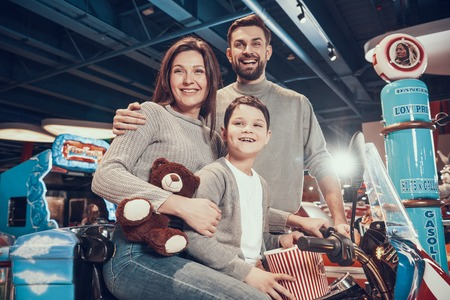 Happy family sitting on toy motorbike. Rest, holiday, leisure. Spending time together. Entertainment center, mall, amusement park.