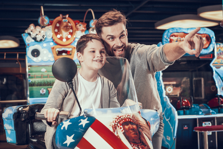 Father and son on toy motorcycle. Family rest, leisure concept. Spending holiday together with family. Entertainment center, mall, amusement park.