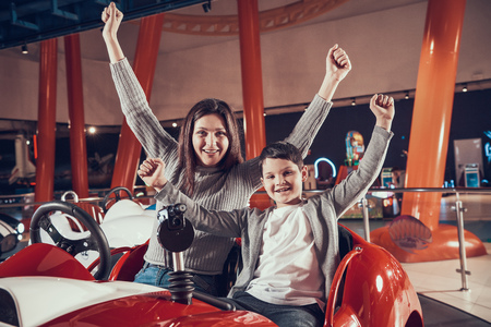 Happy smiling mother and son sitting on toy car. Spending holiday together with family. Entertainment center, mall, amusement park. Family rest, leisure concept. Archivio Fotografico