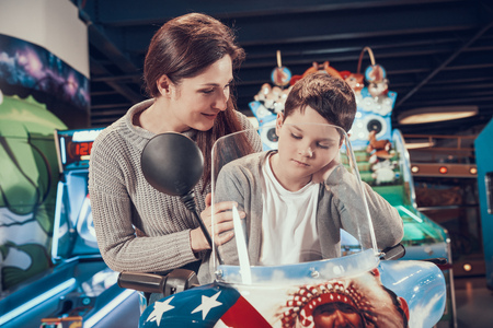 Mom and son in amusement park on toy motorbike. Family rest, leisure. Spending holiday together with family. Entertainment center, mall, amusement park. Stock Photo