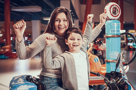 Happy mom and son on toy motorcycle. Family rest, leisure. Spending holiday together with family. Entertainment center, mall, amusement park. 写真素材 - 103343267