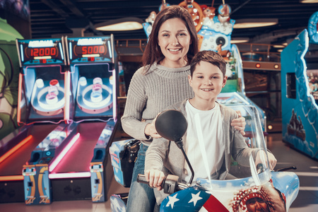 Happy mom and son in amusement park on toy motorcycle. Rest, holiday, leisure. Spending time together. Entertainment center, mall, amusement park.