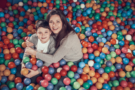 Top view. Smiling mom and son in pool with balls hugging each other. Family rest, leisure. Spending holiday together with family. Entertainment center, mall, amusement park.