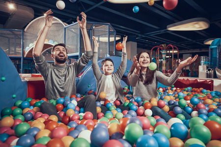 Happy family sitting in pool with balls. Family rest, leisure. Spending holiday together. Entertainment center, mall, amusement park. Banco de Imagens - 103343273