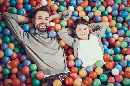 Top view. Happy dad and son in pool with balls. Family rest, leisure concept. Spending holiday together. Entertainment center, mall, amusement park. Stock Photo